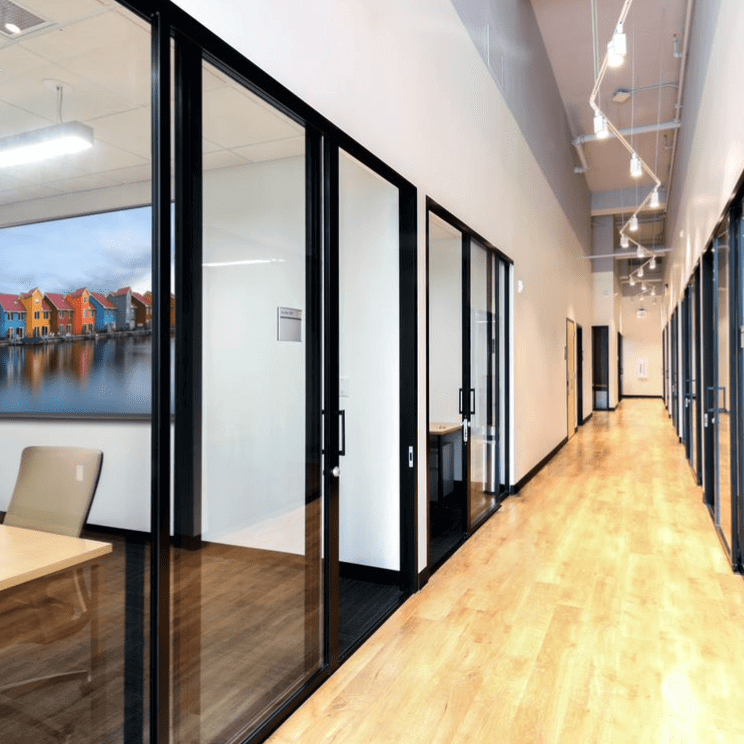 Office hallway with transparent glass doors in left and right cubicles