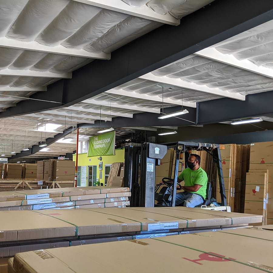 A warehouse man operating a forklift inside a room filled with boxes of doors