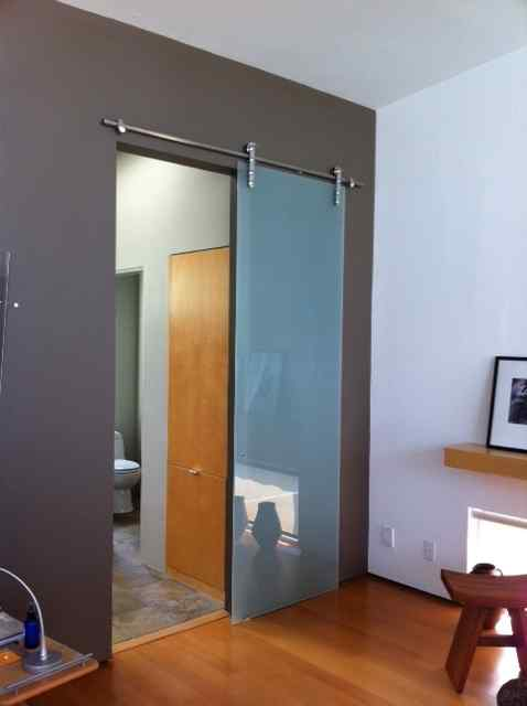 Frameless barn door bathroom glass