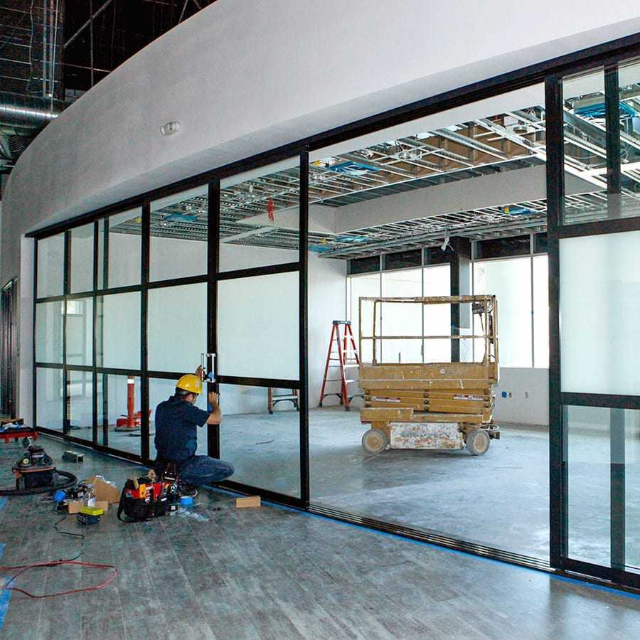 A man installing glass doors for a commercial space